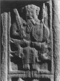 Plate 1: Seated chief bearing upright sword, circular shield and spear under the arm: south face of the high cross at Durrow, County Offaly. (COURTESY OF THE OFFICE OF PUBLICWORKS)