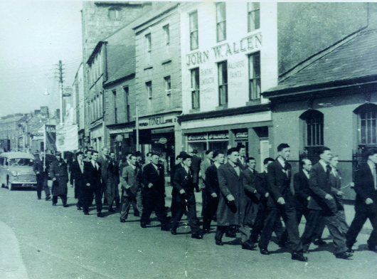 Seán South (circled) marching in the 1956 Easter Rising commemoration in Limerick. At the bottom left-hand corner is the badge worn by all IRA volunteers during the 1956–62 border campaign. (Des Long)