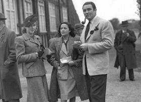The 'Gorgeous Gael', Jack Doyle, with his wife Movita (centre) and friend at the Phoenix Park races c. 1945—'He wears an orange tie knotted in the Duke-of-Windsor manner and a suit which is so draped in shape that it is far more characteristic of Lenox Avenue, New York, than O'Connell Street, Dublin.' (RTÉ Stills Library)
