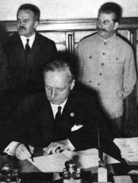Ribbontrop, the German foreign minister, signing the Nazi–Soviet pact on 23 August 1939. Soviet foreign minister Molotov and Stalin stand in the background. (Interfoto)