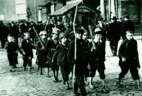 Following the creation of two paramilitary forces—the Ulster Volunteers and the Irish Volunteers—much of Irish society became militarised; young men marched, drilled and prepared for conflict, as did these barefoot Dublin inner-city children. (George Morrison)