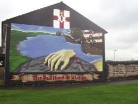 A literal (and slightly disturbing!) depiction of the origin of the Red Hand of Ulster image in a loyalist mural off Belfast's Lower Shankill Road. Coats of arms often pun by alluding to the name of the family concerned, known as 'the canting of arms', and the use of distinctive Gaelic features is well represented by the heraldic emblem of the Uí Néill. According to tradition, Heremon, the third son of Milesius and first Uí Néill king of Ireland, resolved a dispute with a rival king by staging a boat race in which the winner would be the one who touched dry land first. When his opponent built up a lead, Heremon had to act fast. He drew his sword, cut off his right hand and threw it onto the shore, thereby establishing the royal line of Uí Néill descendants who ruled over large parts of Ireland for centuries. This imagery would not have been lost on Ó Maolchonaire, whose own family were hereditary genealogists and chroniclers. O'Farrell's Linea Antigua genealogy states that Ó Maolchonaire's family were amongst the 'kings, nobility and gentry of Leinster, Conaght, Ulster Scotland &c. descended from Heremon, third son of Milesius of Spain'.