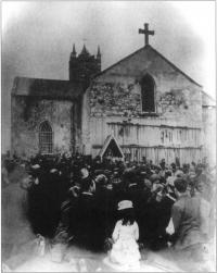 An open air Mass at the shrine c.1880. Note the rows of crutches abandoned by disabled people who believed themselves cured and the extent to which the wall has been denuded of plaster by pilgrims eager for relics.(Sean Sexton collection)