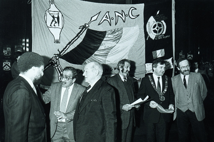Lord Mayor Bertie Ahern, flanked by actor Ger O'Leary (right) and ANC representative Aziz Pahad (left), hosts a celebration of the ANC's 75th anniversary in Dublin's Mansion House in December 1986. To the left is the Nigerian ambassador in conversation with Kader Asmal and actor Cyril Cusack. (An Phoblacht)