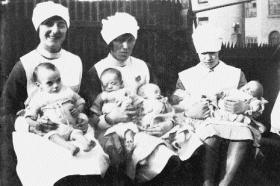 Infants (l–r) Betty, George, Jack, Kate and Joseph with unnamed nurses, March 1929. (Teach Ultáin Infant Hospital)