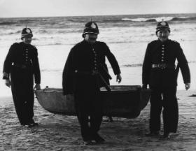 RIC constables seize a small boat found at Banna Strand, Co. Kerry, following the landing of Sir Roger Casement. (RTÉ Stills Library)
