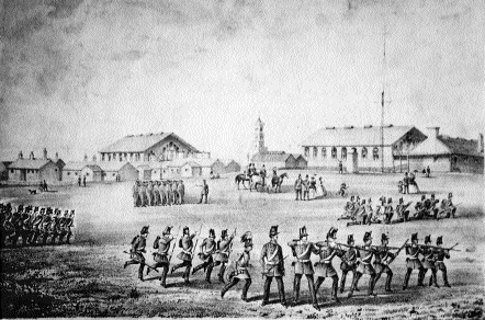 The Curragh Camp headquarters c. 1860-a group of officers and their ladies watch a section of infrantrymen drilling while another practices musketry.
