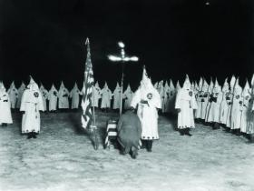 Ku Klux Klan initiation ceremony, 1920s—Coyle openly denounced it as 'un-American', and became a figure of hate. (Jack Benton—Hulton Archive/Getty Images)