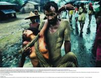 Refugee camp in Calcutta in 1971. A Bangladeshi man carries his cholera-stricken wife—just two of the estimated nine million people who fled the war across the border into India. (Mark Edwards/Still Pictures)