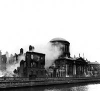 The Four Courts under bombardment. The explosion that ripped through its Public Record Office on 30 June 1922 destroyed much of Ireland's documentary heritage dating back to the early thirteenth century. (RTÉ Cashman Collection)