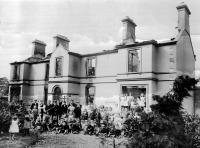 The gutted ruins of the parochial house following attacks on Catholic-owned property in Lisburn in August 1920. A disturbing feature is that the crowd in front (including women and children) is a loyalist one (note the Union Jack) clearly proud of its handiwork in the cold light of day. (Mooney Collection)