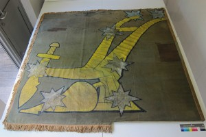 Before conservation—the flag had been mounted back to front on an old mount board that was too small for the object. (Rachel Phelan)