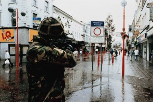 'A British soldier checks distant activity . . . during a patrol in the centre of Newry'—official British Army photograph, undated but probably the 1980s. (Imperial War Museum)