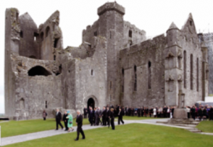 Queen Elizabeth II (related to Edmund MacRichard through her mother) visiting the Rock of Cashel in 2011. As a child, MacRichard was fostered by the archbishop of Cashel, Richard O'Hedian, responsible for various repairs and extensions, including this fortified western end of the cathedral. (Con Brogan/DAHG)