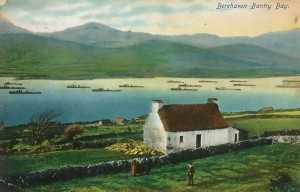There is much about this picture that is typical of the Irish postcard. Even today, a century after this photograph was taken and coloured, you would not have to search long for a similar scene of a whitewashed thatched cottage with deep blue water behind it and the green hills rising in the background. The destroyer flotilla in the middle ground isn't quite so typical these days, but in the early years of the twentieth century the might of the Royal Navy was something commonly seen in Irish waters. In the case of Berehaven, it was not just the odd destroyer force that briefly dropped anchor in Bantry Bay:  battleships, and indeed whole battle squadrons, were regular visitors, for these were home waters to the British Home Fleet, and the Atlantic was the exercise ground and playground of all the terrible great ships of which HMS Dreadnought was only the most famous. (Fergus O'Connor/Adrian Healy