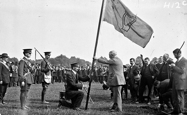 Above: John Redmond presenting a regimental flag bearing a harp to a unit of the National Volunteers in the Phoenix Park in April 1915. (NLI)